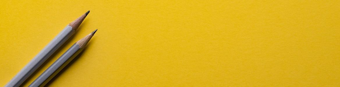 Dos lápices sobre un fondo amarillo