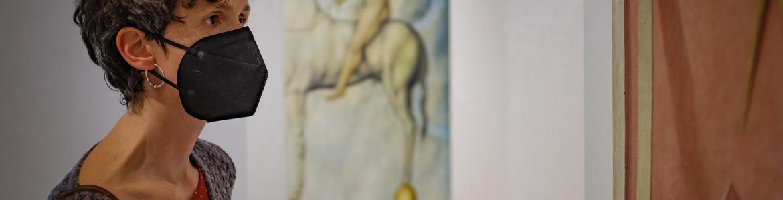 Mujer con mascarilla frente a un cuadro