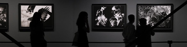 Cuatro personas viendo las fotografías en blanco y negro de David Jiménez en la sala de exposiciones de Canal