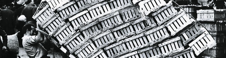 Fotografía en blanco y negro de un hombre transportando muchas cajas de productos que parece se le van a caer encima