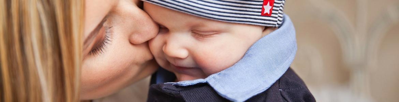Madre con niño en los brazos dándole un beso