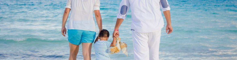 Familia en la playa cogidos de la mano. El bebé, en medio, sujeta un peluche