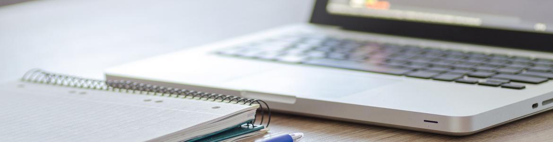 Ordenador, libreta y bolígrafo