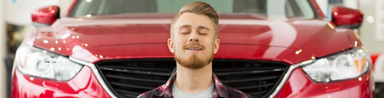 Señor meditando sentado delante de un vehículo rojo