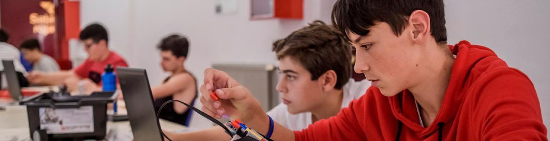 Jóvenes con piezas de Lego y ordenadores