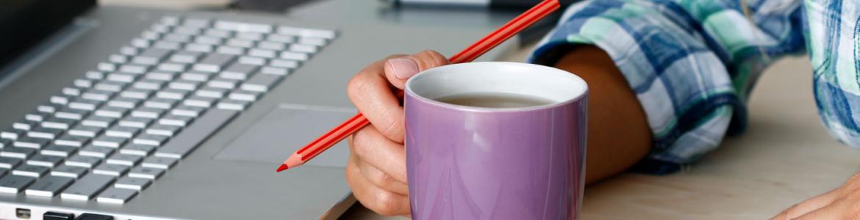 Brazo de una persona con un lápiz en la mano coge una taza encarnada junto a un portátil y cuadernos