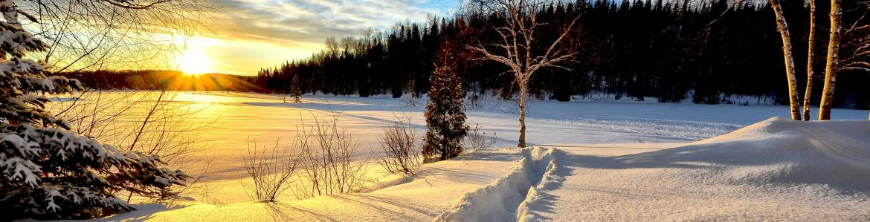 Paisaje nevado con un sendero marcado en la nieve al atardecer