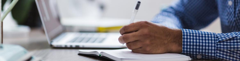 Persona haciendo anotaciones en una libreta