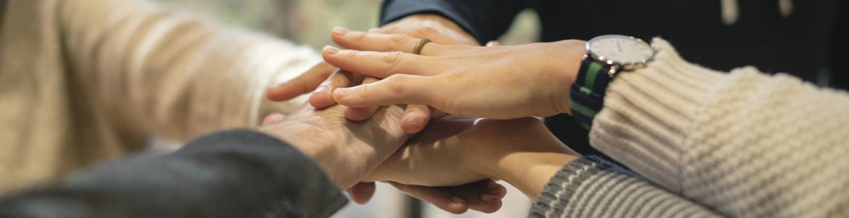 Grupo de personas poniendo mano sobre mano