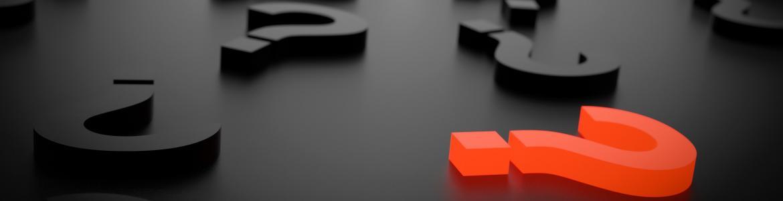 Signos de interrogación negros sobre fondo negro y uno de ellos en color rojo