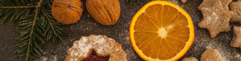 Bodegón de alimentos: nueces, naranja cortado, pastas y rama de abeto