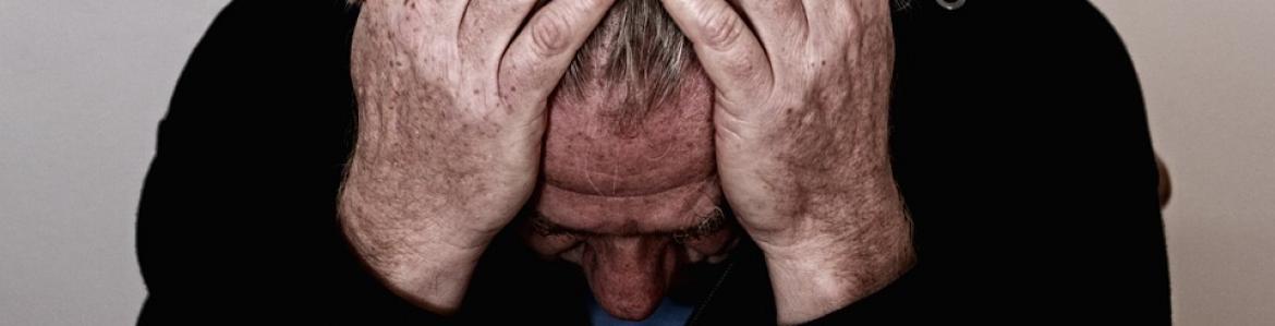 Hombre mayor con la cabeza entre las manos