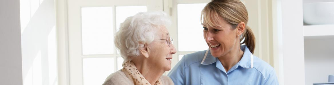 Mujer mayor caminando junto a enfermera