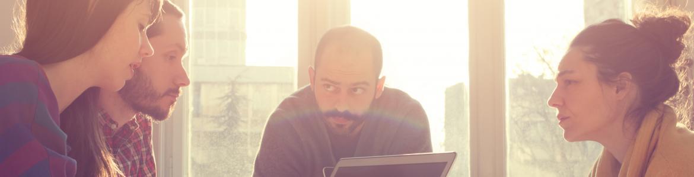 Personas sentadas alrededor de una mesa, en la que hay un portátil, durante una reunión de trabajo. Al fondo, un ventanal deja ver el exterior de la calle