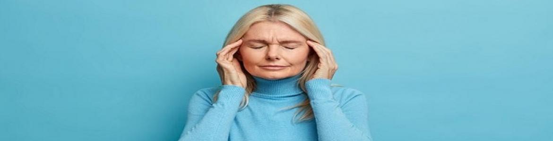 Mujer con jersey azul sujetándose la cabeza con los ojos cerrados y un gesto de dolor