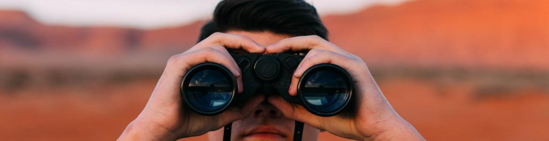 Joven mirando por unos prismáticos