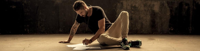 Chico sentado en el suelo revisando papeles