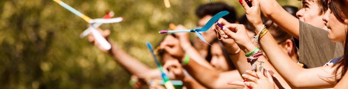 Jóvenes lanzando al aire cintas de colores