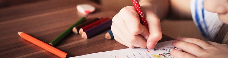 niña escribiendo en una hoja sobre una mesa