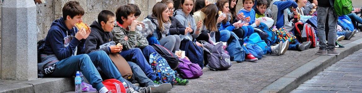 Niños sentados a las puertas de un museo