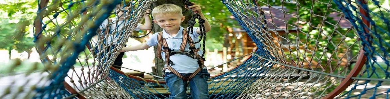 Niño pequeño dentro de un circuito de tirolinas