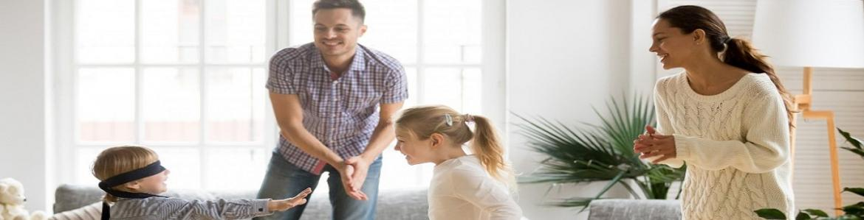 Mujer, hombre, niña y niño jugando a la gallina ciega en una sala de estar