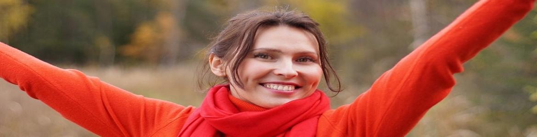 Mujer con jersey rojo sonriendo con los brazos en alto