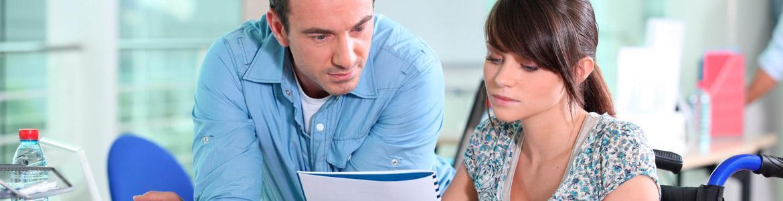 Mujer con discapacidad consultando documentos junto a un compañero