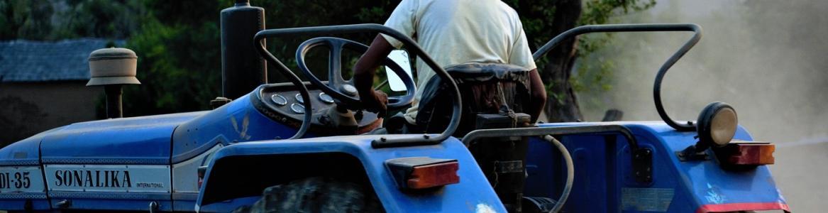 Agricultor de espaldas conduciendo un tractor azul sin capota en sus labores en el campo