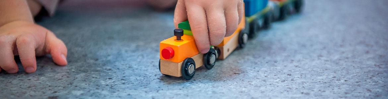 Detalle de la mano de un bebé que juega con un tren de madera