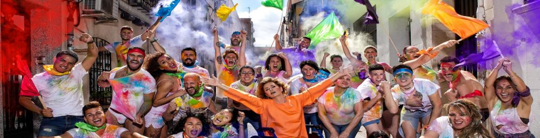 Grupo de personas con banderas y atuendo multicolor
