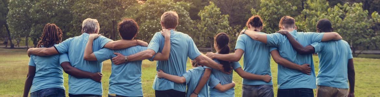Voluntarios de espaldas abrazados