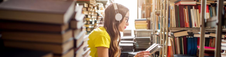 Chica de pelo largo y con gafas sentada entre pilas de libros
