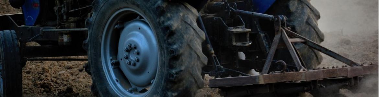 persona trabajando sobre un tractor azul