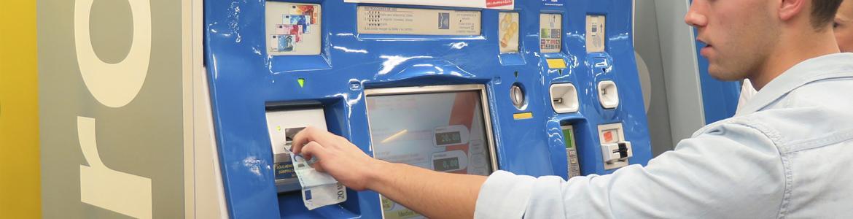 Imagen de hombre joven introduciendo un billete en una máquina expendedora de Metro