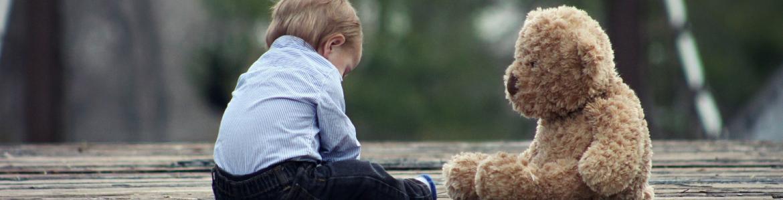 Niño jugando con un oso de peluche