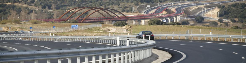 imagen con varias carreteras, coche circulando y un puente