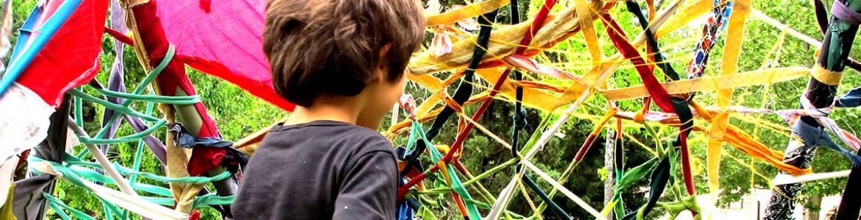 Niño con un telar grande de tejido reciclado