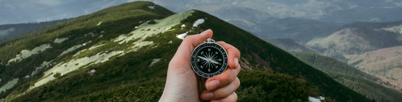 mano sosteniendo una brújula con paisaje de montaña al fondo