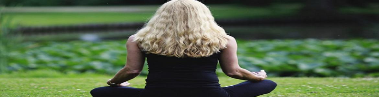 Mujer meditando sobre cesped