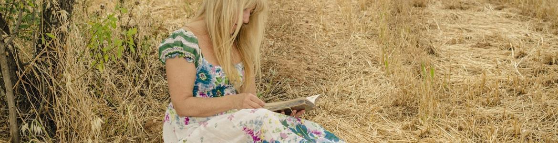 Chica leyendo libro en el campo