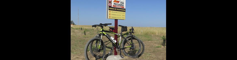 """Bicicleta apoyada en el cartel de inicio de la vía pecuaria """"Vereda de Villaviciosa"""""""