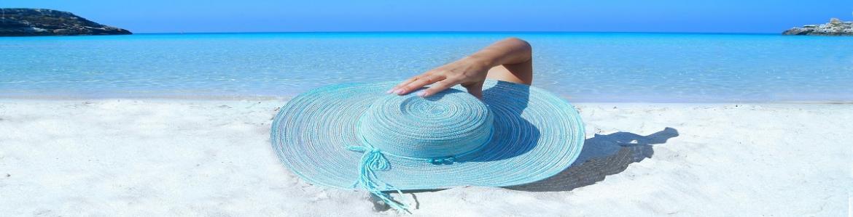 Persona tumbada en la playa con sobrero azul y mar al fondo