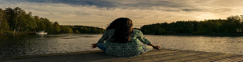 Mujer meditando frente a un lago