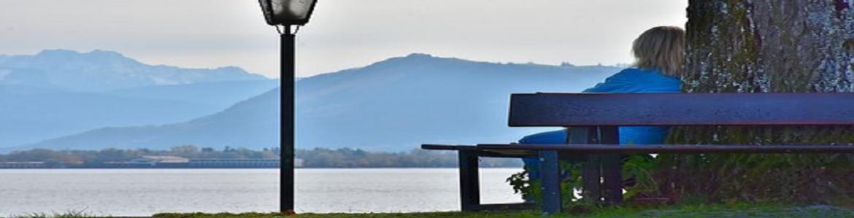 Mujer sentada en un banco junto a un lago