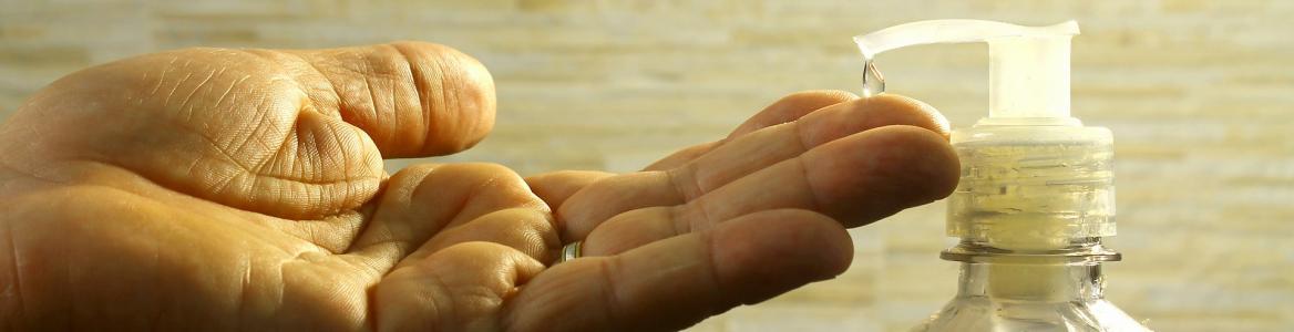 mano de hombre abierta para recoger una gota de gel de un dispensador
