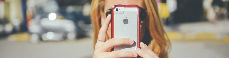 Chica con un móvil en alto tapándole la cara