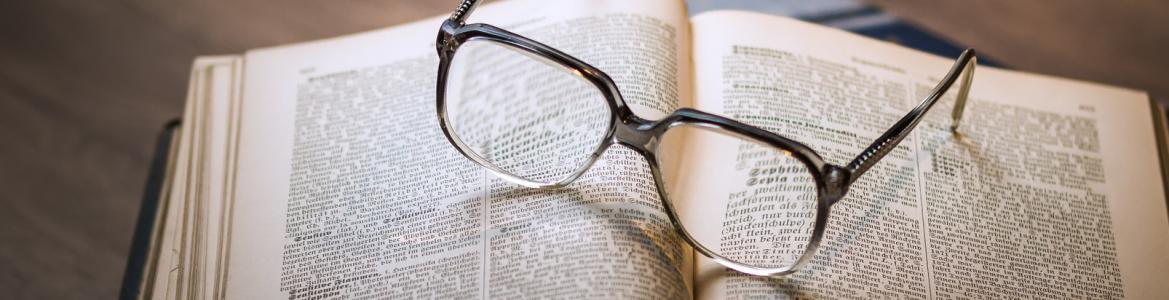 Libro abierto con gafas sobre él