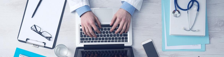 Médico escribiendo en ordenador