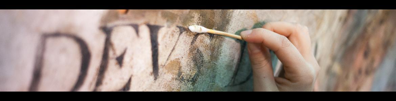 Detalle de mano restaurando una pintura